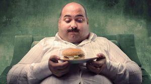 Obézní muž sedí a hladově kouká na hamurger ve svých rukou.